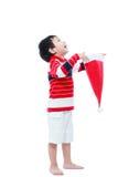 Chapéu feliz de Santa da posse do menino no fundo branco Imagens de Stock