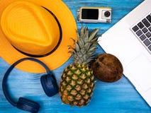Chapéu, fones de ouvido, câmera da ação, portátil, abacaxi e coco fotos de stock