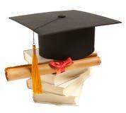 Chapéu, livro e diploma da graduação Foto de Stock Royalty Free