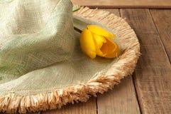 Chapéu verde com o Tulip amarelo na madeira rústica Fotografia de Stock