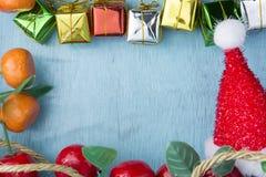 Chapéu vermelho das caixas de presente e da Santa Claus em de madeira ciano imagens de stock