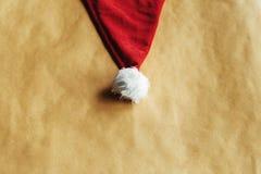 Chapéu vermelho do Natal à moda bonito em um envoltório bonito do feriado do ofício foto de stock