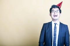 Chapéu vestindo asiático do partido do homem de negócio Imagem de Stock
