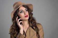 Chapéu vestindo da beleza pensativa séria que fala no telefone que olha afastado imagens de stock