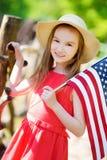 Chapéu vestindo da menina adorável que guarda a bandeira americana fora no dia de verão bonito Fotos de Stock