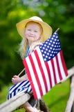 Chapéu vestindo da menina adorável que guarda a bandeira americana fora no dia de verão bonito Foto de Stock Royalty Free