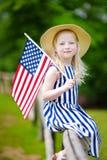 Chapéu vestindo da menina adorável que guarda a bandeira americana fora no dia de verão bonito Imagens de Stock Royalty Free