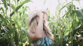 Chapéu vestindo da menina bonita e corrida de sorriso em um movimento lento de campo de milho filme