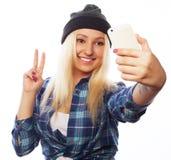 Chapéu vestindo da menina consideravelmente adolescente, tomando selfies Imagens de Stock