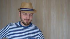 Chapéu vestindo do homem novo do turista pronto para férias contra o fundo cinzento filme
