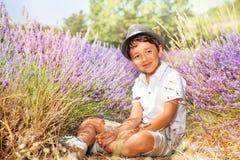 Chapéu vestindo do rapaz pequeno, sentando-se no campo da alfazema Imagem de Stock