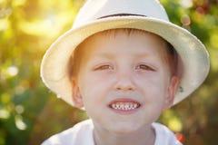 Chapéu vestindo e sorrisos do menino bonito Árvore no campo Rapaz pequeno caucasiano em um chapéu do verão fora foto de stock