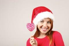 Chapéu vestindo fêmea do ` s de Santa do ruivo lindo com o PNF-pom, comemorando feriados festivos da estação do inverno fotos de stock