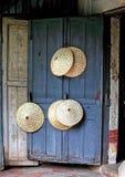 Chapéus da máquina desbastadora do arroz na porta azul Imagem de Stock Royalty Free