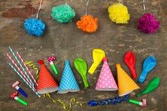 Chapéus do feriado, assobios, balões no fundo de madeira velho Imagens de Stock
