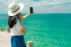 Chap?u asi?tico novo do desgaste de mulher no smartphone do uso do estilo ocasional que toma o selfie no cais F?rias de ver?o na  fotografia de stock royalty free