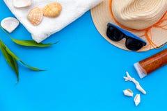 Chap?u de palha, vidros de sol, escudos e creme do sunblock para f?rias do mar no espa?o azul da c?pia da opini?o superior do fun foto de stock