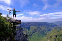 The cliffs of the Cachoeira Da Fumaca, Smoke Waterfall, with a hiker standing on the edge, Vale Do Capao, Bahia, Brazil. Chapada Diamantina landscape and the stock photos