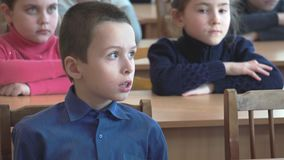Schoolboy listens to the teacher. CHAPAEVSK, SAMARA REGION, RUSSIA - FEBRUARY 02, 2018: School kids of elementary school sit at desks in the classroom. The stock video footage