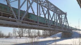 Train rides in winter on the railway bridge. Chapaevsk, Samara Region, Russia - March 28, 2018: Passenger Train rides in winter on the railway bridge stock video footage