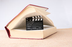 Chapaleta de la película al lado de un libro en una lona Fotografía de archivo libre de regalías