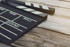 Chapaleta de la película en la tabla de madera imagen de archivo