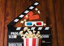 Chapaleta de la película, palomitas, vidrios 3d en un de madera Imagen de archivo libre de regalías