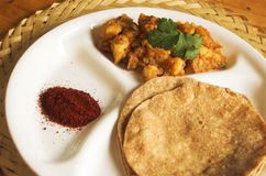 Chapathi and curry indian food. Chapathi / roti (a type of indian bread) and curry made of potatoes, onions and tomatoes with chutney powder on the side Royalty Free Stock Photo