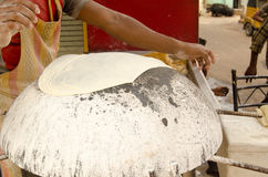 Chapati Bread making, Hyderabad. A baker using a hot stone to bake chapati bread at a roadside stall in Hyderabad, India Stock Images