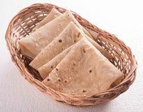 Chapati dans le panier sur le fond blanc image libre de droits