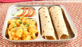 Chapati or Indian Flat Bread. Chapati, also known as Indian flat Bread, with cauliflower curry as a side dish and slices of cucumber and tomato, in a steel plate Royalty Free Stock Photography