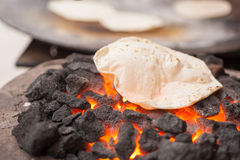 Chapati (Indian flatbread). A roti (Indian flatbread) cooking on a coal fire stock image