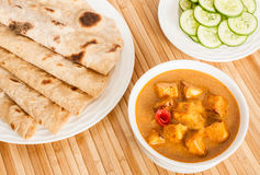 Chapati with Indian Paneer Butter Masala. Folded homemade wheat chapati (Indian bread) served with delicious Indian paneer butter masala and cucumber salad. It Stock Photo