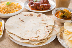Chapatti roti. Curry chicken, biryani rice, salad, masala milk tea and papadom. Indian food on dining table royalty free stock image