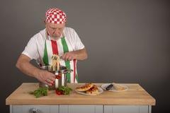 Chapeamento italiano maduro do cozinheiro chefe acima de um prato da massa fotos de stock royalty free