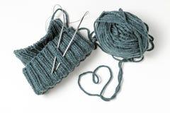Chapeau, aiguilles de tricotage et écheveau tricotés sur un fond blanc photo stock