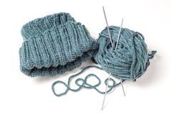 Chapeau, aiguilles de tricotage et écheveau tricotés sur un fond blanc image libre de droits