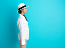 Chapeau blanc de fond bleu de jeune femme, chemise photographie stock libre de droits
