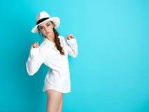 Chapeau blanc de fond bleu de jeune femme, chemise photos stock