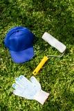 Chapeau bleu, rouleau de peinture et gants fonctionnants blancs sur l'herbe verte Images libres de droits