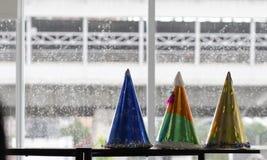 Chapeau coloré de confettis et de partie à la maison, fond de pluie, partie c photographie stock libre de droits