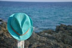 Chapeau d'été de paille sur le pilier et la mer en bois Photos libres de droits