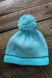 Chapeau d'hiver de turquoise sur un fond en bois d'isolement Photos stock