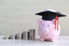 Chapeau d'obtention du diplôme sur la tirelire rose avec la pile d'argent de pièces de monnaie sur le fond en bois, argent économ image stock