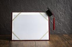 Chapeau d'obtention du diplôme sur le concept d'éducation de certificat d'obtention du diplôme sur en bois avec le fond foncé image libre de droits