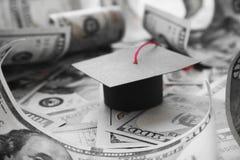 Chapeau d'obtention du diplôme d'université de Loan Debt With d'étudiant sur l'argent dans noir et blanc images stock