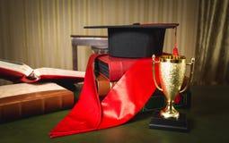 Chapeau d'obtention du diplôme, ruban rouge et tasse d'or pour le premier endroit Photographie stock libre de droits