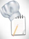 Chapeau de chef avec le cahier de recette Photo stock