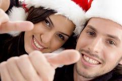 chapeau de couples de Noël semblant les jeunes s'usants Images libres de droits