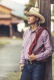 Chapeau de cowboy de port de jeune homme beau se tenant pensant Images libres de droits